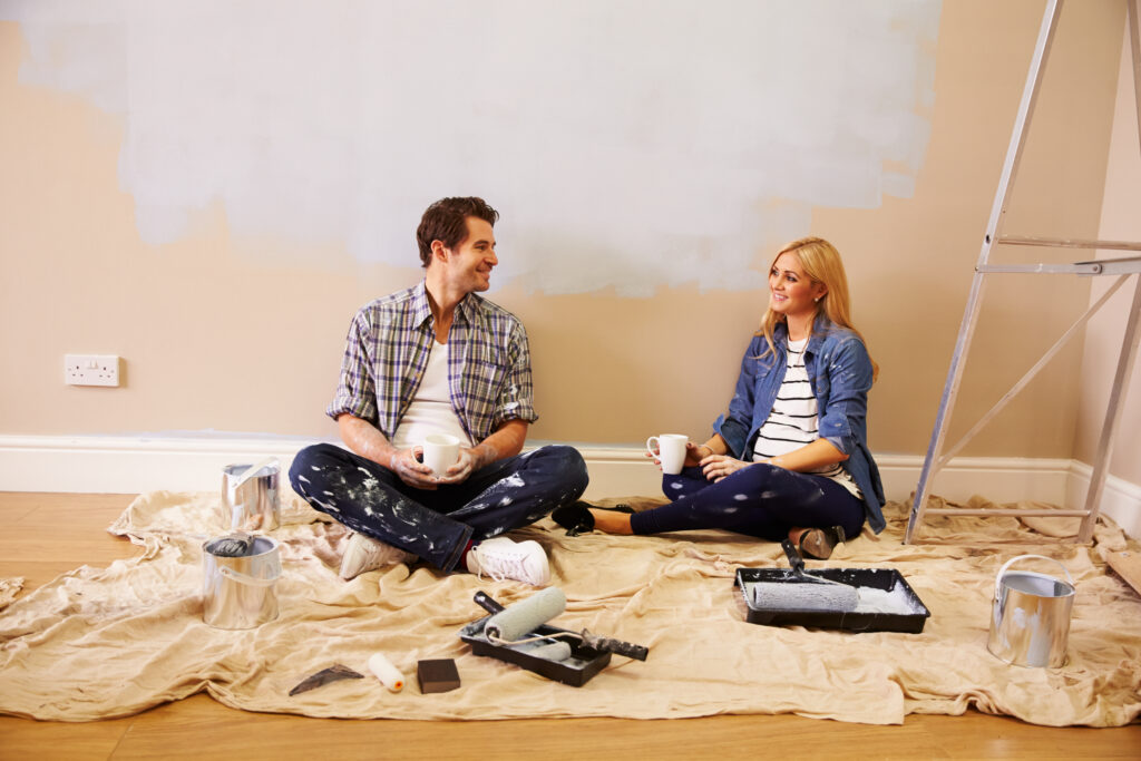Expectant Couple Taking A Break Whilst Decorating Nursery. Image credit: iStock