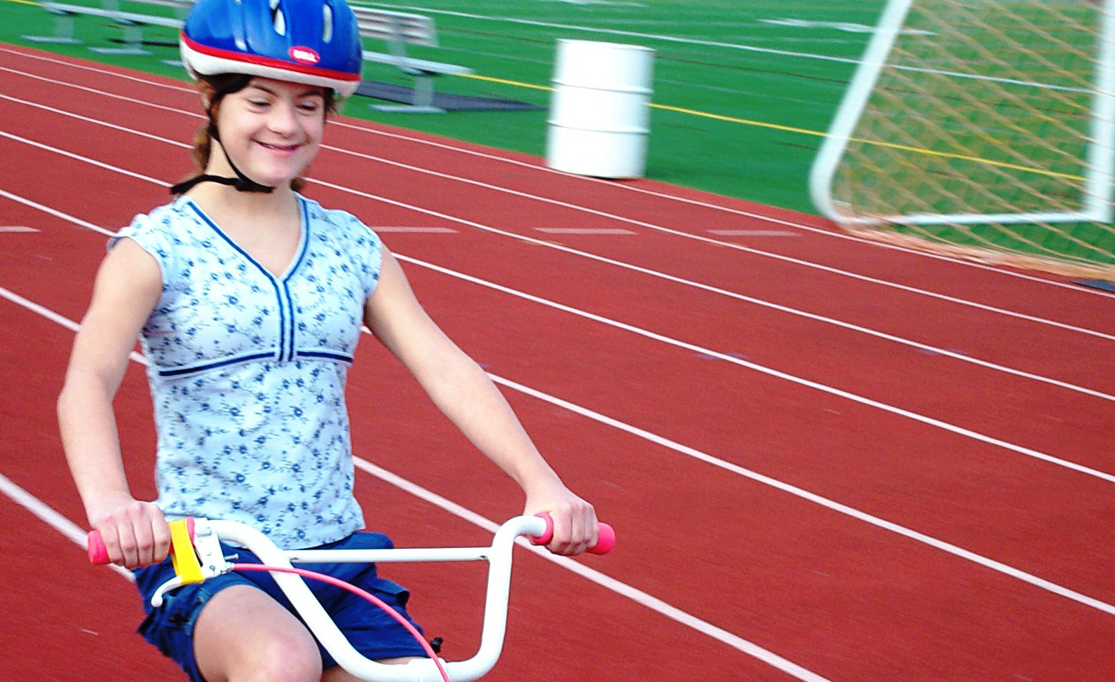 University of Michigan School of Kinesiology bike camp participant Bridget Richards zooms around happily on her two-wheel bike. Richards was part of the 'bike camp' study conducted by U-M Kinesiology. The study looked at the feasibility and benefit of teaching children with Down syndrome to ride two-wheel bikes. U-M Kinesiology teamed with the nonprofit group Lose the Training Wheels, which provided the specially designed bikes and the individualized training. The majority of participants learned to ride after five consecutive days of 75 minute individualized training sessions. Photo courtesy of Greg and Mary Anne Richards