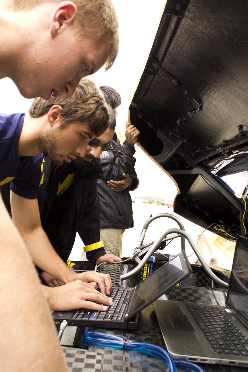 University of Michigan solar car team race crew members Santosh Kumar, Aeresh Bilmoria, Jordan Feight and AJ Trublowski check under the hood during a control stop on a practice race in Australia. Credit: Evan Dougherty