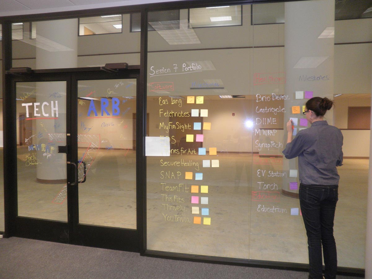 A record number of student-run companies is sharing space in the University of Michigan's TechArb business accelerator. Gillian Henker, with the company DIIME, puts a note on the incubator window. Photo courtesy of Malvika Bhatia