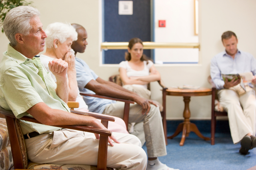 Several people wait in a doctor's office reception area