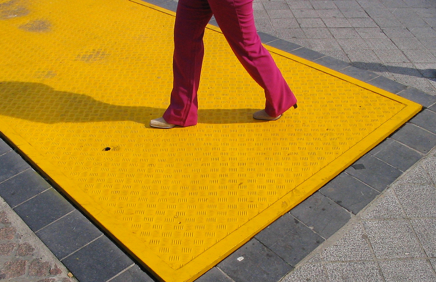 Pink-clad pants walking over bright yellow access panel. Image courtesy of sxc.hu user pixelbox