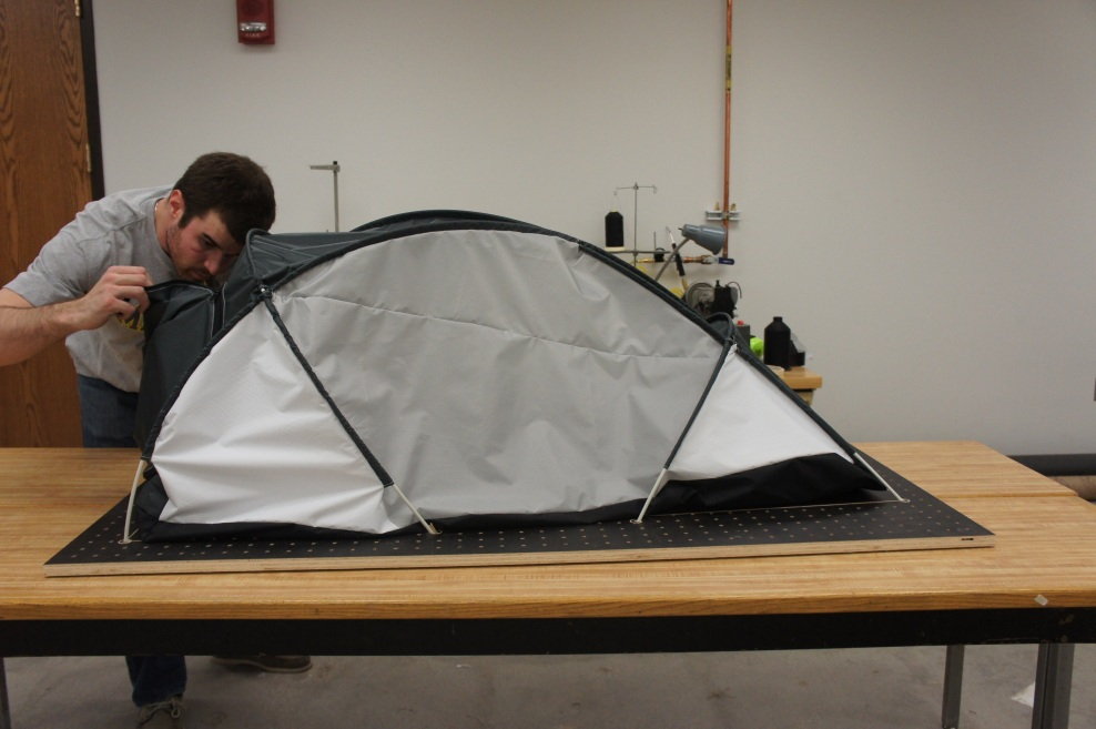 Andrew McCarthy puts the finishing touches on a half-scale model of a  tent he designed for his climbing expedition. Image credit: Andrew McCarthy