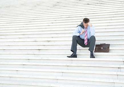 Businessman hangs his head on a set of bleak white steps