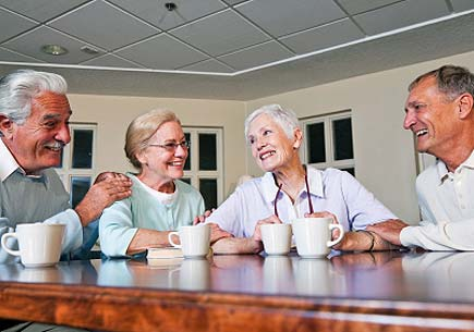 Two senior couples drinking coffee together in community center. (stock image)