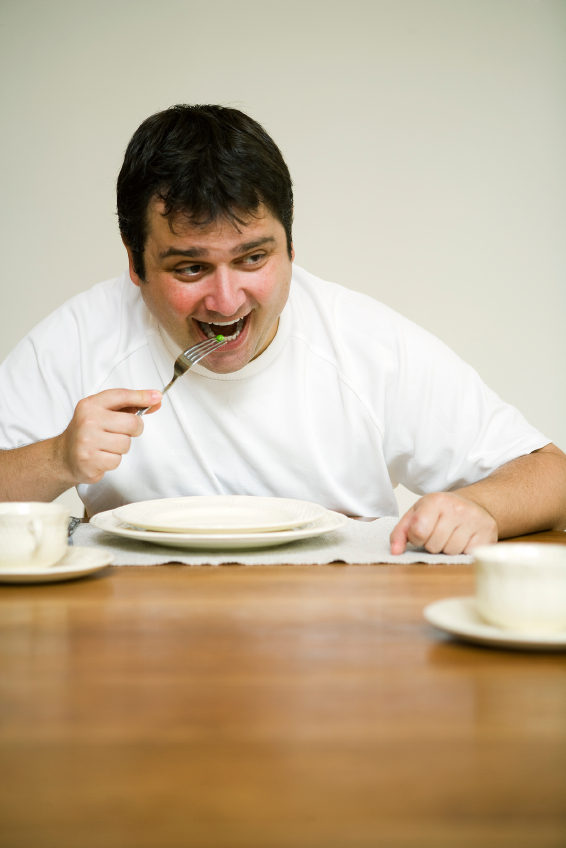 Unconvinced man with a green pea for lunch. (stock image)