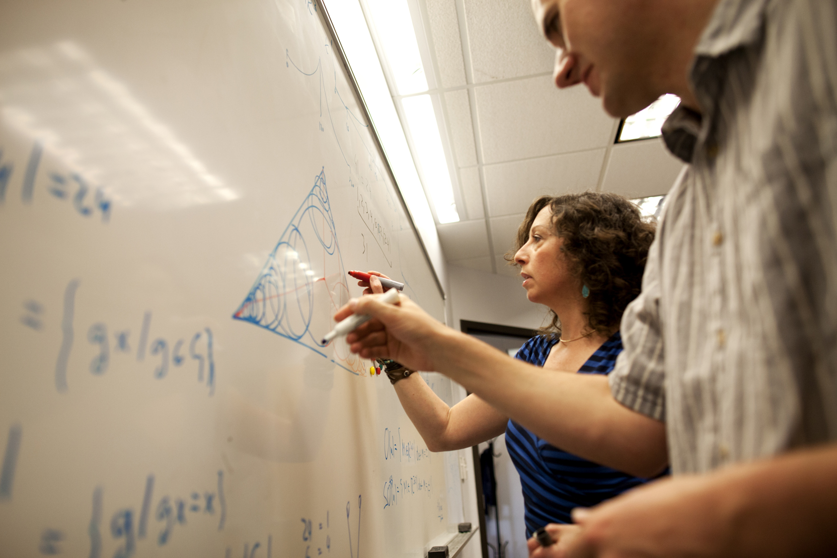 Joshua Anderson (left) and Sharon Glotzer, members of The Glotzer Group in the Laboratory for Computational Nanoscience & Soft Matter, demonstrate their new mathematical problem: the best way to fill a space with overlapping shapes while respecting the boundary. Image credit: Joseph Xu, College of Engineering