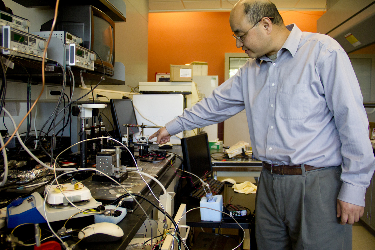 Xudong Fan, an associate professor of biomedical engineering, points to the compressor that is part of the smart, portable gas sensor that he is developing. The device could one day be used to detect chemical weapon vapors or indicators of disease more precisely than current models do. It also consumes less power, which is crucial for stretching battery life in a mineshaft or an isolated clinic. Image credit: Joseph Xu, College of Engineering