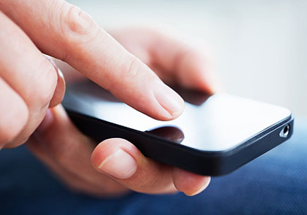 Close-up shot of hands of a businessman using a smartphone. (stock image)