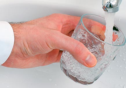 Photo of a hand filling a glass with tap water. Image credit: sxc.hu user ArtMast