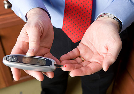 A businessman checks his blood glucose level. (stock image)