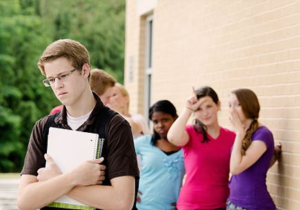 A group of teens make fun of another student outside of a school. (stock image)