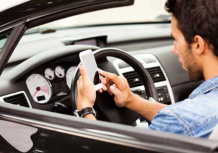 Close up of a young man using smart phone in his car. (stock image)