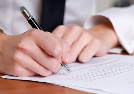 Person's hand signing an important document (stock image)