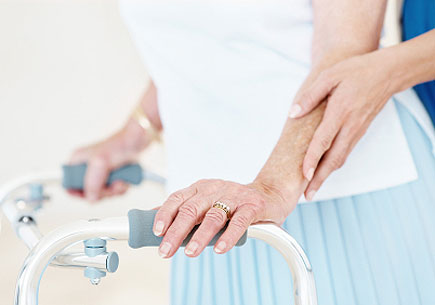 A close-up of a young woman's hands and an old lady's hands using a walker as support. (stock image)