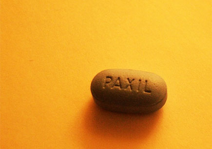 Image of a pill tablet on a yellow background. Image credit: flickr.com user ~!