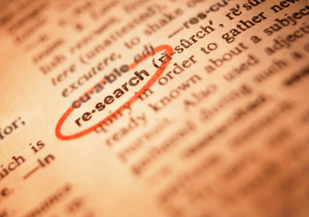 Text on a page with the definition for the word research circled in red (stock image)