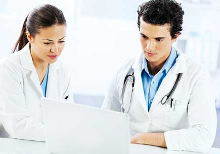 Young doctors working together, they are using a laptop. (stock image)