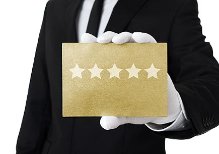 Human hand holding gold card with five stars on it. (stock image)