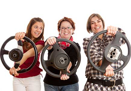 Three women holding steering wheels. (stock image)