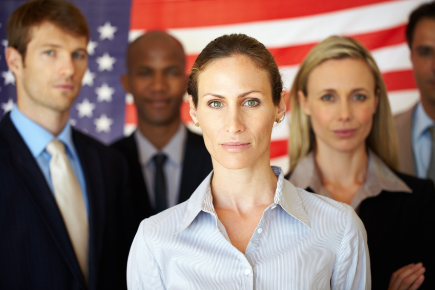Portrait of several men and women standing with flag in the background (stock image)