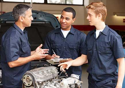 Mechanic training apprentices in workshop (stock image)