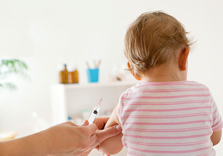 Back view of baby girl patient receiving vaccine at the doctor's office. (stock image)