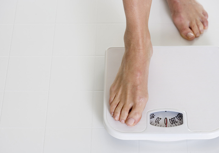 Stepping onto a scale. (stock image)