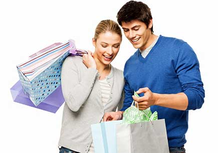 A man and woman happily holding and looking into shopping bags. (stock image)
