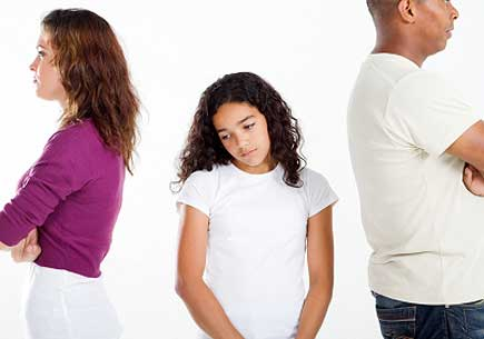 Unhappy girl standing between ather and mother. (stock image)