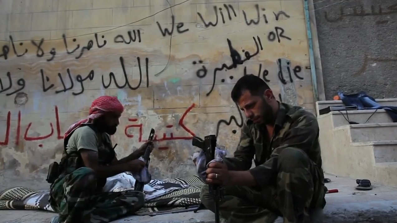 FSA rebels cleaning their AK47s in Aleppo, Syria during the civil war. Image credit: VOA News; Scott Bobb reporting from Aleppo, Syria
