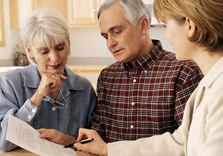 Mature couple talking to financial planner at home (stock image)