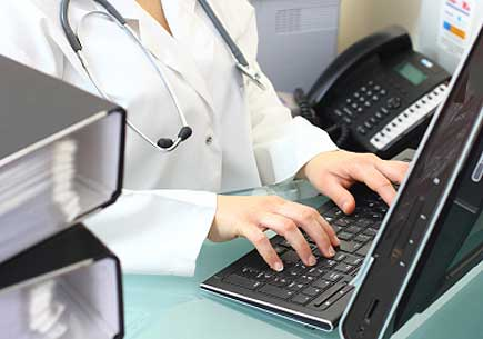 Cropped photo of a person wearing a lab coat and stethoscope typing on computer keyboard. (stock image)