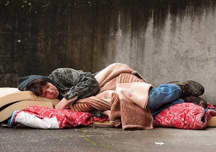 Homeless woman lying on the street. (stock image)