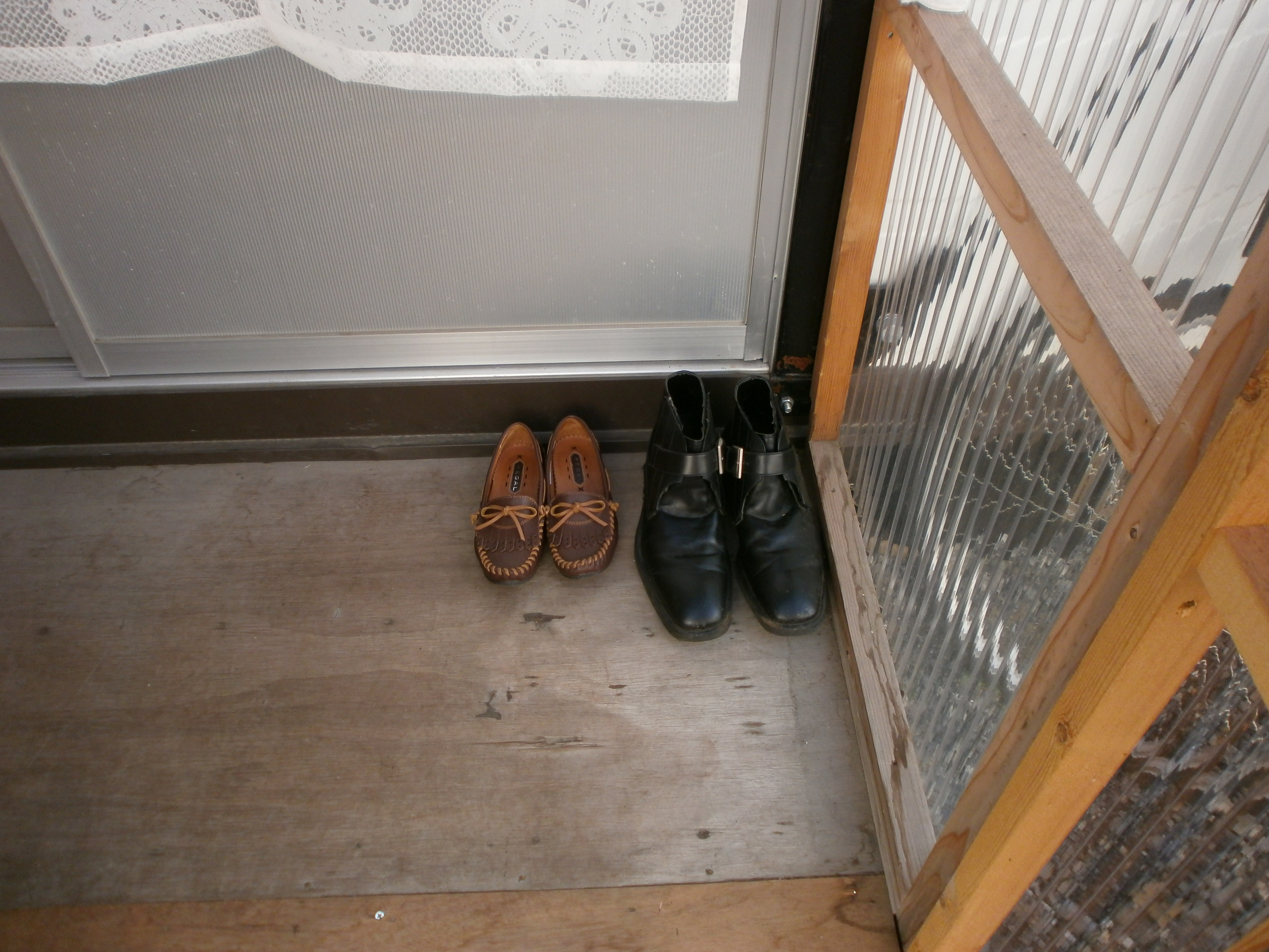 A large pair of men's shoes beside a smaller ladies pair of shoes near front door. Image credit: William Foreman