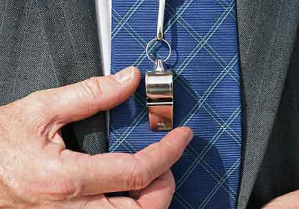 Businessman's' shirt and suit lapels shown with his hand on a silver whistle resting on the tie (stock image)
