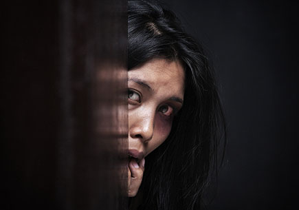 Abused woman hiding in dark, concept for domestic violence (stock image)