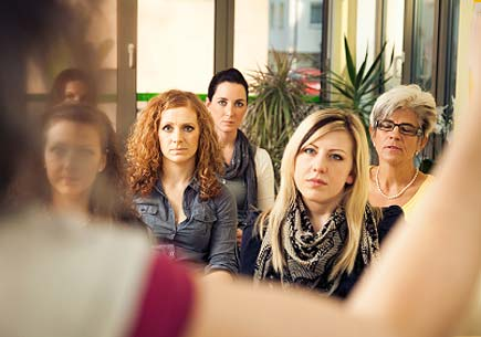 A group of professional women listening to a speaker. (stock image)