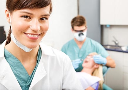 A portrait of a dental assistant smiling at the camera with the dentist working in the background. (stock image)