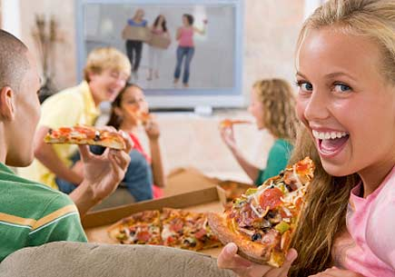 Teenagers hanging out in front of the television eating pizza. (stock image)