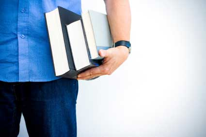Cropped image of a male hand holding several books against his hip. (stock image)