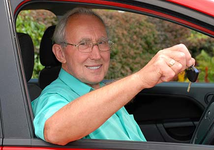 A senior man sits in a car smiling and holding up a set of keys. (stock image)