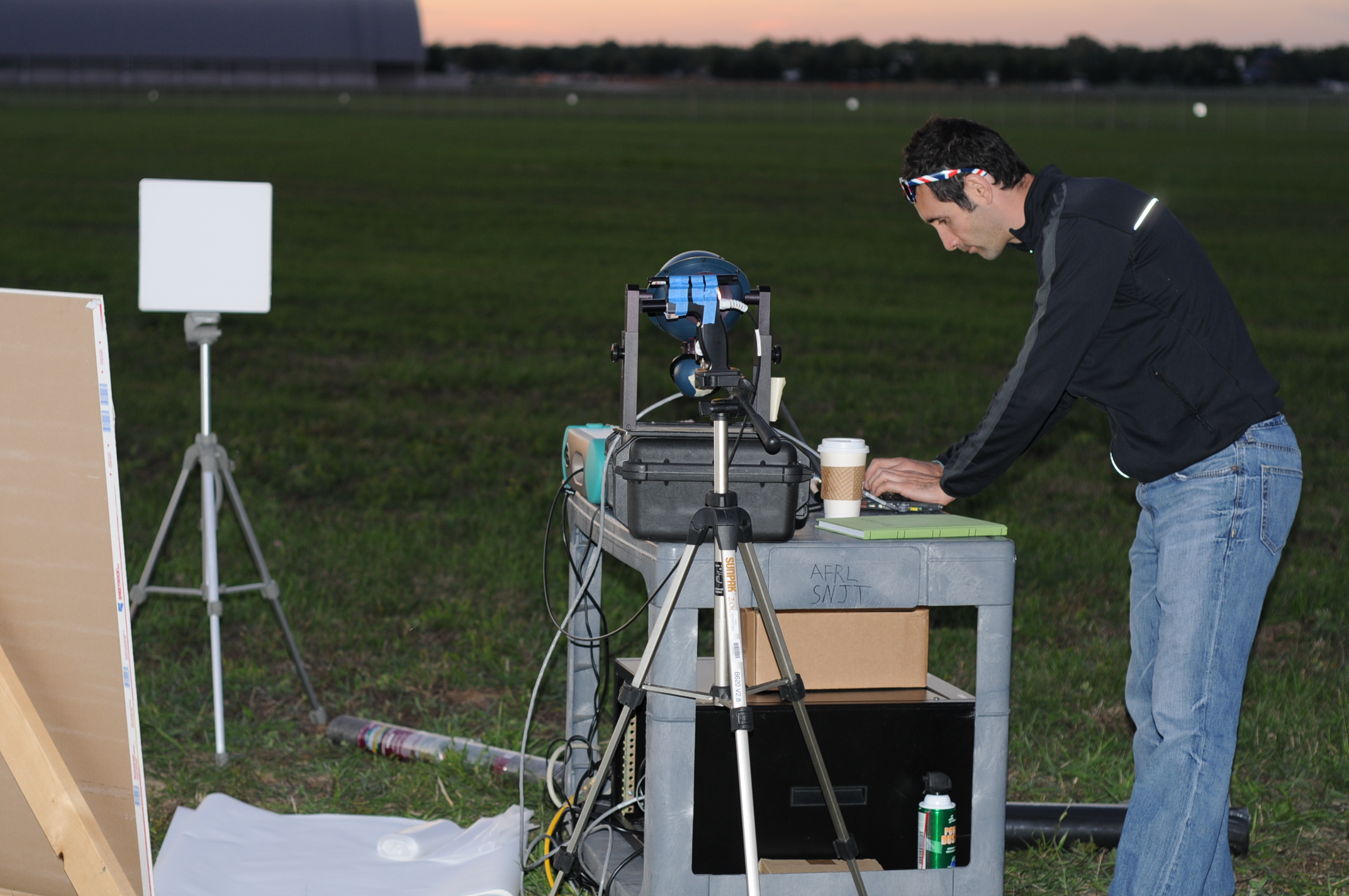 Joseph Meola of Air Force Research Labs conducting measurements on laser light bounced back from various samples placed 1.6 kilometers on the ground from a prototype laser at Wright Patterson Air Force Base. Image credit: Anthony Absi, Air Force Research Labs