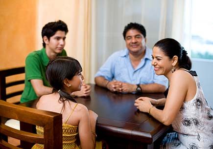 A family chatting at the dinner table. (stock image)