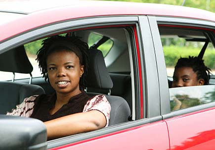 A woman driving with her child in the back seat. (stock image)