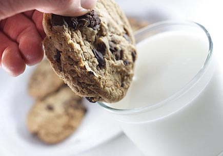 Dipping a cookie into a glass of milk. (stock image)