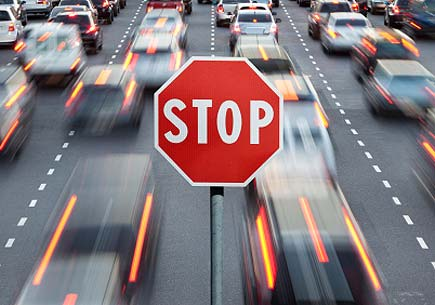 A stop sign superimposed over motion blurred cars on a highway. (stock image)