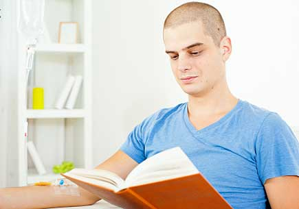 Young man having chemotherapy treatment at home and reading a book. (stock image)
