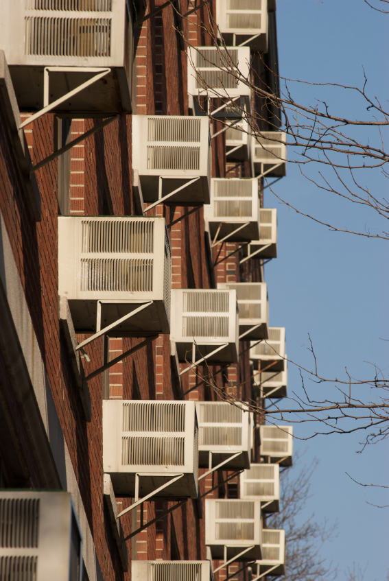 Building in the city with several window air conditioners. (stock image)