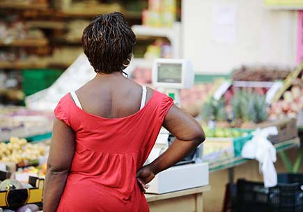 Rear view of an African American woman surveying a market's produce section. (stock image)